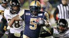 Winnipeg Blue Bombers' Chad Simpson (5) dodges the tackle from Hamilton Tiger-Cats' Jamall Johnson (28) and Matt Bucknor (26) during the second half of their CFL game in Winnipeg Friday, September 21, 2012. (The Canadian Press)