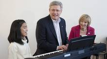 Prime Minister Stephen Harper sings 'Imagine' with 10-year-old Maria Aragon as Laureen Harper looks on during a campaign stop in Winnipeg, Tuesday March 29, 2011. Aragon shot to fame after posting a video on YouTube that was praised by musician Lady Gaga. (Adrian Wyld/The Canadian Press/Adrian Wyld/The Canadian Press)