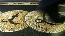 An employee is seen walking over a mosaic of pound sterling symbols set in the floor of the front hall of the Bank of England, in London in this March 25, 2008 file photograph. (© Luke MacGregor / Reuters/REUTERS)
