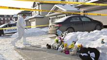 Flowers and stuffed animals lay on the sidewalk as police continue to investigate the scene where multiple shooting deaths occurred in Edmonton Dec. 31, 2014. (Jason Franson/The Canadian Press)