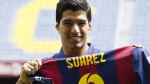 FC Barcelona's Luis Suarez holds up his jersey during his presentation at the Nou Camp stadium in Barcelona August 19, 2014. Suarez was officially presented as a Barcelona player on Tuesday while he is still banned for biting Giorgio Chiellini in Uruguay's World Cup game with Italy on June 24. (GUSTAU NACARINO/REUTERS)