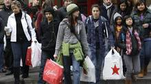 Shoppers carry their bags as they walk in downtown Seattle in this 2010 file photo. (Ted S. Warren/Ted S. Warren/AP)