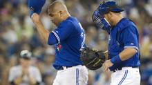 Toronto Blue Jays catcher Jeff Mathis (right) talks to pitcher Ricky Romero after New York Yankees Russell Martin walked during second inning American League action in Toronto on Friday August 10 , 2012. (Chris Young/THE CANADIAN PRESS)