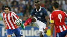 French soccer team midfielder Paul Pogba, centre, challenges for the ball with Paraguayan soccer team forward Roque Luis Santa Cruz Cantero, right, and midfielder Fidencio Oviedo Martinez, during the friendly soccer match between France and Paraguay at the Allianz Riviera Stadium, in Nice, southeastern France, Sunday, Juin 1, 2014. (Associated Press)