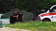 Police officers talk in front of a emergency services tent next to the Algo Centre Mall in Elliot Lake, Ont., on June 24, 2012. (Chad Valiquette/THE CANADIAN PRESS)