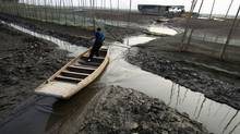 A fisherman tries to paddle his boat through a small stream amid the partly dried-up Honghu Lake in Honghu, Hubei province. (STRINGER/CHINA/REUTERS)