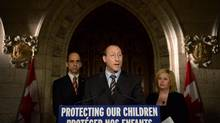 Peter MacKay, Minister of Justice and Attorney General of Canada speaks as Steven Blaney, Minister of Public Safety and Emergency Preparedness, back right, Lianna McDonald, Executive Director of the Canadian Centre for Child Protection, join him in announcing a proposed cyberbullying law on Parliament Hill in Ottawa on Nov. 20, 2013., as part of Bullying Awareness Week. Critics say the proposed law revives an old controversy around a withdrawn Internet-surveillance bill known as Bill C-30. (Sean kilpatrick/THE CANADIAN PRESS)