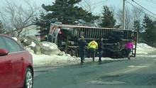 """People look on as a truck lies on its side in Paradise, N.L. on Saturday, March 11, 2017 in this handout photo. Police in Newfoundland and Labrador are urging drivers to stay off the roads while emergency crews work to contain the damage caused by """"extreme"""" winds. (Troy Mitchell/THE CANADIAN PRESS)"""