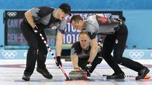 Canada's skip Brad Jacobs delivers the rock while Ryan Harnden, left, and E.J. Harnden, right, sweep the ice during the men's curling competition against Denmark at the 2014 Winter Olympics, Thursday, Feb. 13, 2014, in Sochi, Russia. (Wong Maye-E/AP)