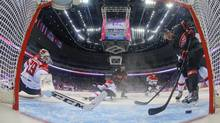 Canada forward Jeff Carter scores against Austria goaltender Bernhard Starkbaum in the second period of a men's ice hockey game at the 2014 Winter Olympics, Friday, Feb. 14, 2014, in Sochi, Russia. (Mark Blinch/AP)