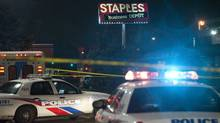 Police investigate the scene where a woman was killed by flying debris near Keele Street and St. Clair Avenue during a storm in Toronto on Monday, October 29, 2012. Police believe it was the other side of the Staples sign that was found nearby.  (Matthew Sherwood for The Globe and Mail)