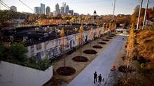 In this Nov. 20, 2012 photo, a couple walks along the Atlanta BeltLine as the midtown skyline stands in the background in Atlanta. (David Goldman/The Associated Press)
