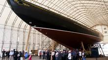 The Bluenose II was initially scheduled to be launched in early July, but that has been pushed back. Shipbuilders look on from below the bow of Bluenose II at a shipbuilding announcement in Lunenburg, N.S. on Friday, July 7, 2012. The sailing icon, which is undergoing a complete rebuild, is expected to be back in the water before the end of the year. (Andrew Vaughan/Canadian Press)