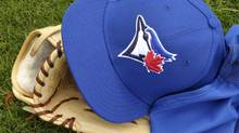 A Toronto Blue Jays players cap and glove rest on the field (MIKE CASSESE/REUTERS)