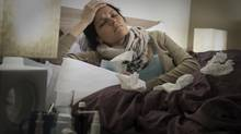 A woman lies in bed holding her head with used tissues littering the bed cover. (J.M. Guyon/iStockphoto)