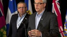 Manitoba Premier Greg Selinger, right, reports on the impact of proposed changes to federal transfers to the provinces, as Nova Scotia Premier Darrell Dexter looks on at the annual Council of the Federation meeting in Halifax on Friday, July 27, 2012. (Andrew Vaughan/THE CANADIAN PRESS)