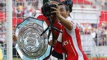 Arsenal's Santi Cazorla, right, takes a selfie with Alex Oxlade-Chamberlain as they celebrate their win against Manchester City with the trophy at the end of their English Community Shield soccer match at Wembley Stadium in London, Sunday, Aug. 10, 2014. (Sang Tan/AP)