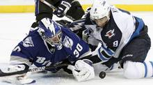 Tampa Bay Lightning goalie Dwayne Roloson (30) battles with Winnipeg Jets left wing Evander Kane (9) for a loose puck during the first period of an NHL hockey game on Saturday, Oct. 29, 2011, in Tampa, Fla. (AP Photo/Chris O'Meara) (Chris O'Meara/AP)