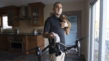 Adam Sax runs a drone company that serves the oil and gas industries, but he is encountering resistance to new technologies. He is seen here with his puppy, Muchkin, at his company's headquarters in Oakville, Ont. (J.P. MOCZULSKI/The Globe and Mail)