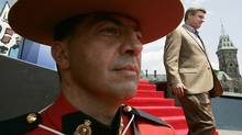 Prime Minister Stephen Harper walks past a mountie after addressing a crowd on Parliament Hill in Ottawa Saturday, July 1, 2006. (Jonathan Hayward/ The Canadian Press/Jonathan Hayward/ The Canadian Press)