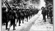 Canadian troops march past Sir Robert Borden in France on July 1, 1918. The prime minster angered rural Canadians when he broke a promise not to conscript farmers. (National Archives of Canada)