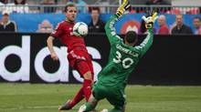 Toronto FC's Jeremy Brockie, left, fails to score on Columbus Crew's goaltender Andy Gruenebaum, right, during the first half of the Trillium Cup match MLS action in Toronto on Saturday, July 27, 2013. (Michelle Siu/THE CANADIAN PRESS)