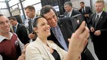Republican presidential candidate, former Pennsylvania Sen. Rick Santorum stops for a phone picture with Erica Marple, of Marietta,Ga., while campaigning at Peachtree DeKalb Airport, Thursday, March 1 , 2012. (John Amis/AP/John Amis/AP)