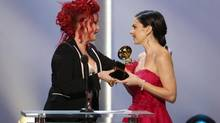 Cyndi Lauper, left, presents the best children's album award to Jennifer Gasoi for Throw A Penny In The Wishing Well at the pre-telecast of the 56th annual Grammy Awards on Jan. 26, 2014. (MATT SAYLES/INVISION/ASSOCIATED PRESS)