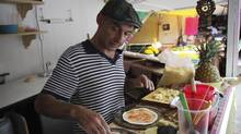 Former freelance photographer Xavi Berdala, 45, of Barcelona, prepares pizza at his pizza stall in Tepoztlan, in the Mexican state of Morelos Oct. 9, 2012. Between 2007 and 2011, the number of native Spaniards emigrating to Mexico rose by 129 per cent. (STRINGER/MEXICO/REUTERS)