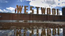 A demolition expert examines the letters atop the old Westwood Theatre on the southeast corner of Kipling Road and Bloor Street. (Peter Power/The Globe and Mail)