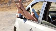 Woman's legs are dangling out a car window during a summer road trip. (Photos.com)