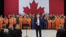 Flanked by British Columbia Institute of Technology heavy duty mechanical trade students, Prime Minister Stephen Harper speaks during an announcement about the apprentice loan program at the BCIT Annacis Island Campus in Delta, B.C., on Thursday January 8, 2015. (DARRYL DYCK/THE CANADIAN PRESS)