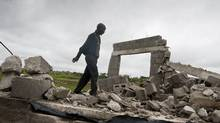Senator Clement, chairman of a residents' committee at KaShali, Swaziland, walks along the ruins of homes that the country's King Mswati III ordered destroyed. (Erin Conway-Smith for The Globe and Mail/Erin Conway-Smith for The Globe and Mail)