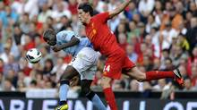 Liverpool's Martin Kelly, right, and Manchester City's Mario Balotelli, left, battle for the ball during their English Premier League soccer match at Anfield in Liverpool, England, Sunday Aug. 26, 2012. (CLINT HUGHES/AP)