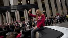 Olympian Clara Hughes waves to crowds along Bay Street in Toronto during a parade celebrating Canada's Olympic athletes Sep 21, 2012. (Moe Doiron/The Globe and Mail)