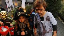 Five-year-old Maya Dumas (L) and her 9-year-old sister Cleo photographed while trick or treating for halloween on Cowan Ave., Toronto October 31, 2012. (Fernando Morales/The Globe and Mail)