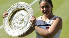 Marion Bartoli of France holds her winners trophy, the Venus Rosewater Dish, after defeating Sabine Lisicki of Germany in their women's singles final tennis match at the Wimbledon Tennis Championships, in London July 6, 2013. (TOBY MELVILLE/REUTERS)