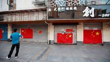 A man looks at large Chinese national flags covering the entrance to a Japanese restaurant in Suzhou, Jiangsu province, Sept. 17, 2012. Major Japanese brand name firms announced factory shutdowns in China on Monday and urged expatriates to stay indoors ahead of what could be more angry protests over a territorial dispute between Asia's two biggest economies. (ALY SONG/REUTERS)