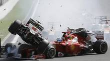 Lotus driver Romain Grosjean, top left, crashes with Ferrari driver Fernando Alonso during the first lap of the Belgium Formula One Grand Prix in Spa-Francorchamps circuit on Sunday, Sept. 2, 2012. (Luca Bruno/AP)