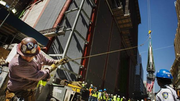 An iron worker uses a line to steady the flag-draped spire before it is lifted to the top of One World Trade Center on Thursday. The final piece helps to fill the void left in the New York skyline by the al-Qaeda attacks of Sept. 11, 2001. (LUCAS JACKSON/REUTERS)