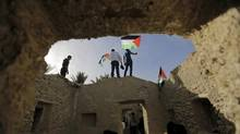 Palestinian and foreign activists hold Palestinian flags as they walk through the structures in an old village known as Ein Hajla, in the Jordan Valley near the West Bank city of Jericho January 31, 2014. Some 100 activists took part in a campaign to try to resettle the village and to protest Israel's occupation of the West Bank including the Jordan Valley. (Ammar Awad/REUTERS)
