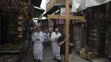 A group of Catholic pilgrims walks past shops selling tourist souvenirs on Via Dolorosa, or the Way of the Cross, believed by Christians to be the route Jesus Christ carried his cross to his crucifixion, in Jerusalem's Old City May 20, 2014. (FINBARR O'REILLY/REUTERS)