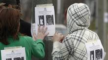 """Cassandra Craig and Shiloh Roth hang a poster for then missing Victoria """"Tori"""" Stafford, 8, on a street corner in Woodstock, Ont. on Friday April 10, 2009. (DAVE CHIDLEY/The Canadian Press/DAVE CHIDLEY/The Canadian Press)"""