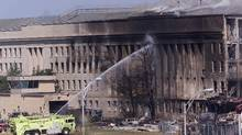An emergency vehicle fights a fire at the Pentagon in Washington 11 September, 2001 hours after a hijacked airplane crashed into the Pentagon. (STEPHEN JAFFE/AFP/Getty Images)