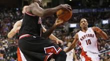 Chicago Bulls forward Luol Deng (9) drives to the net as Toronto Raptors center Jonas Valanciunas (17) and Toronto Raptors guard DeMar DeRozan (10) defend at the Air Canada Centre. Chicago defeated Toronto 96-80. (JOHN E. SOKOLOWSKI/USA TODAY SPORTS)