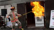 Toronto Fire Services District Chief Peter Derrington prepares a grease fire during a fire safety demonstration. (Moe Doiron/The Globe and Mail)