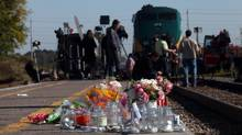 Flowers and candles are left near the scene of the train-bus collision in Ottawa on Sept. 19, 2013. (DAVE CHAN FOR THE GLOBE AND MAIL)