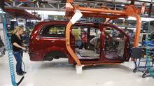 A worker on the production line at Chrysler's assembly plant in Windsor, Ontario, works on one of their new minivans on Tuesday January 18, 2011. (GEOFF ROBINS/THE CANADIAN PRESS)