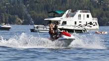 A Jet Ski crosses a houseboat on Shuswap Lake near Salmon Arm, B.C., in July, 2010. (Jeff Bassett for The Globe and Mail)
