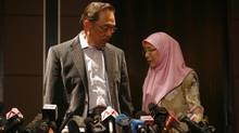 Malaysia's opposition leader Anwar Ibrahim, left, and his wife Wan Azizah Wan Ismail leave after a news conference in Kuala Lumpur on May 6, 2013. Malaysia's ruling National Front coalition won a simple majority of 112 seats in the 222-seat national parliament in Sunday's election, the country's Election Commission said. (Samsul Said/Reuters)
